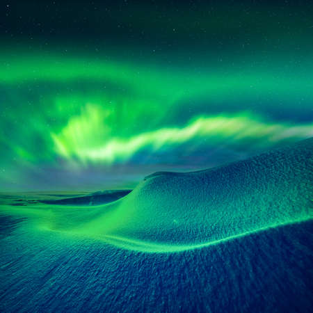 Aurora borealis over fantastic winter landscape in snowy mountains. Dramatic wintry scene with frozen snowy hills and Northern lights. Courtesy of NASA. Photo collage Standard-Bild