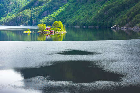 Breathtaking view of small island with red house in Lovrafjorden fjord, Norway. Landscape photography