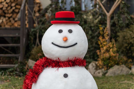Funny snowman in stylish red hat and red scalf on lawn near house. Merry Christmass and happy New Year