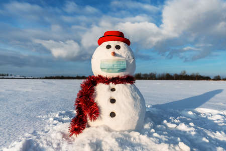 Funny snowman in stylish red hat with medical mask on snowy field. Canceled travel and social distancing concept Standard-Bild