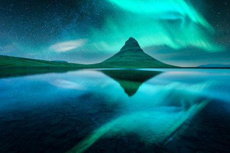 Aurora borealis Northern lights over Kirkjufell mountain volkano. Amazing night scene near famous Kirkjufell waterfall, Iceland. Landscape photography