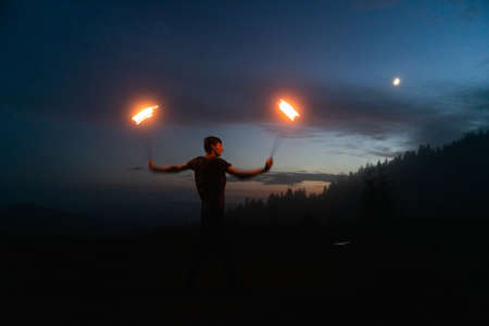 Graceful male fireshow performer making fire dance with two metal fans lit with flames on night mountains meadow Standard-Bild