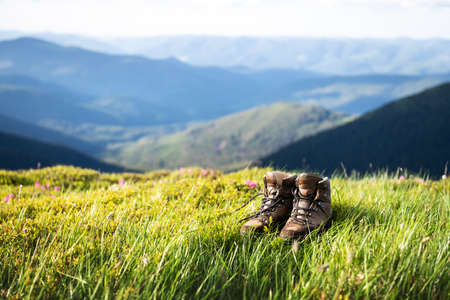 Boots of lonely tourist on lush grass covered mountains hill. Landscape photography Standard-Bild