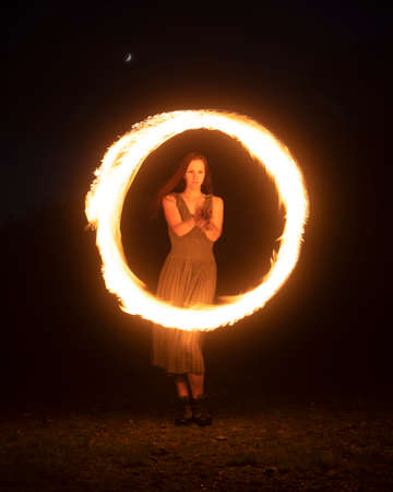 Graceful elegant red haired female fireshow performer making fire dance with two metal fans lit with flames on night mountains meadow Standard-Bild