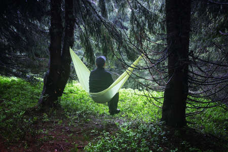 Man on yellow hammock in spring mountains. Travel landscape concept. Outdoor camping