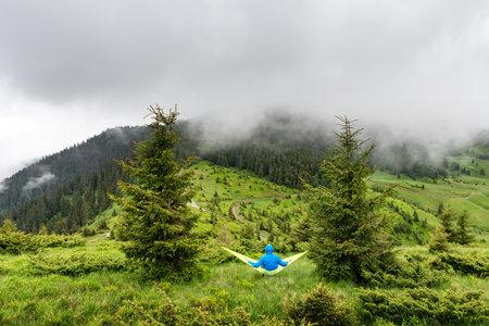 Man on yellow hammock in summer mountains. Travel landscape concept. Outdoor camping Standard-Bild