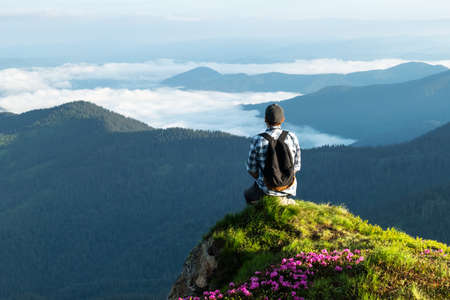 A tourist sits on the edge of a cliff covered with a pink carpet of rhododendron flowers in the summer. Foggy mountains on the background. Landscape photography