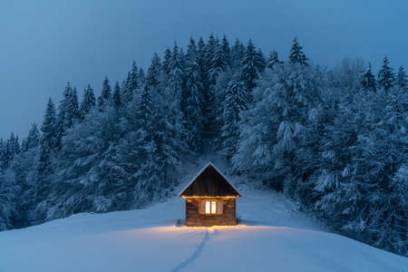 Fantastic winter landscape with glowing wooden cabin in snowy forest. Cozy house in Carpathian mountains. Christmas holiday concept