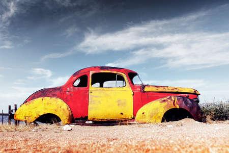 Abandoned derelict old car in the sandy desert Standard-Bild
