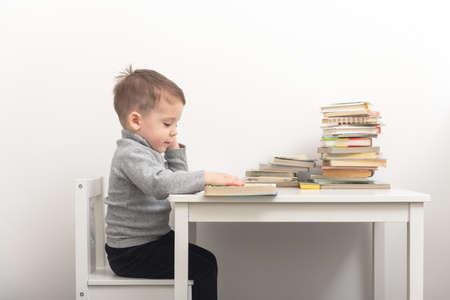 Closeup of cute small boy reading books Standard-Bild