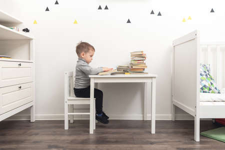 Small boy drawing in his room