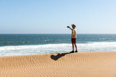 Single man in a cowboy hat takes a selfie in the Namib desert