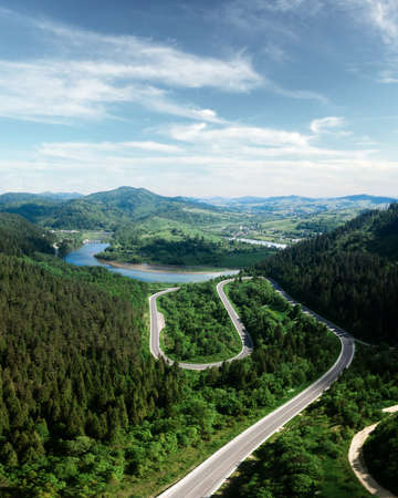 Flight over the summer mountains with mountain road serpentine, river and forest. Ukraine, Carpathian mountains. Landscape photography 版權商用圖片