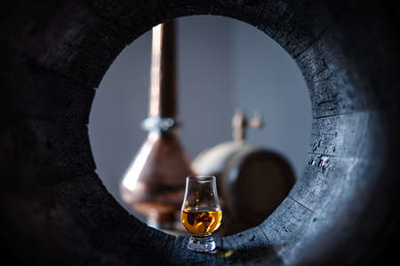 A glass of whiskey in old oak barrel. Copper alambic on background. Traditional alcohol distillery concept 版權商用圖片