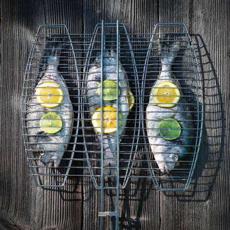 Prepared for grilling dorada fish on wood table