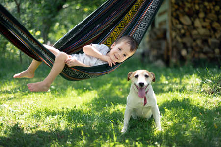 Small kid on hammock with white dog puppy