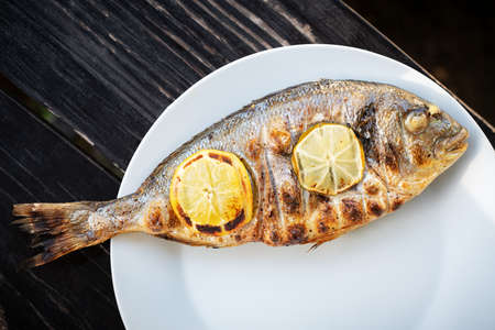 Grilled dorada fish with lemon pieces on white plate