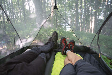 Male legs inside camp tent with summer forest on background