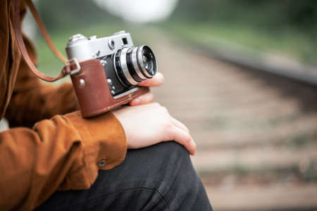 Photographer in brown jacket with retro camera