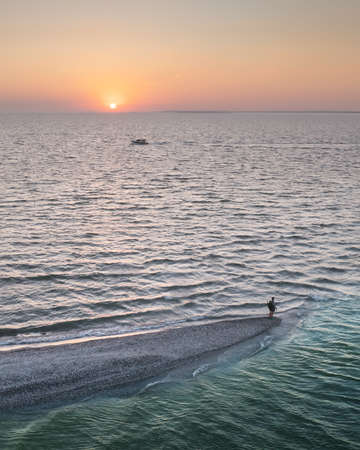 Aerial view over evening sea and spit with tourist