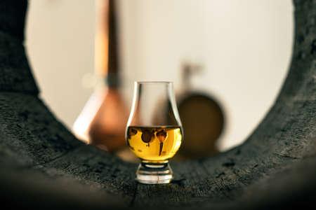A glass of whiskey in oak barrel 版權商用圖片