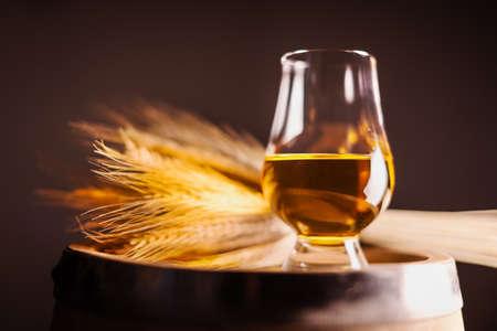 A glass of whiskey on oak barrel 版權商用圖片