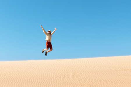 Single man throws sand in the Namib desert