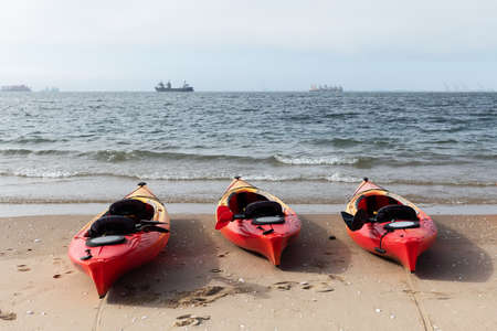 Three red kayaks ready for swimming