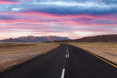 Asphalt road and beautiful landscape with sunset sky