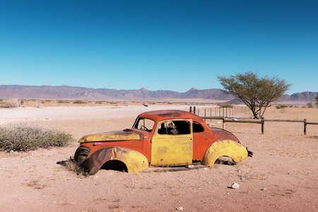Abandoned derelict old car in the sandy desert 版權商用圖片