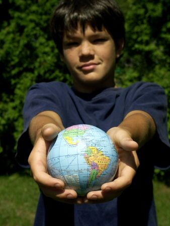 boy holding out the world,focus on the world photo