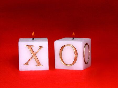 xoxo: isolated over red felt lit up xoxo candles