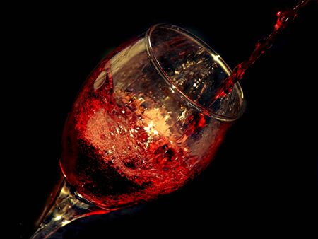 sophistication: red wine being poured in a glass Stock Photo