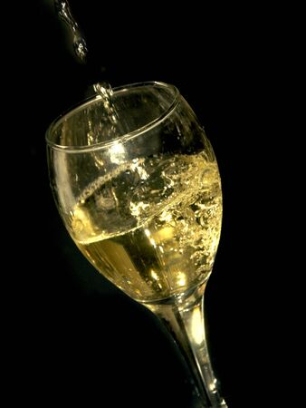 sophistication: white wine being poured in a glass Stock Photo