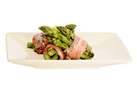 deckled: grilled asparagus wrapped in prosciutto in a deckled bowl isolated on white Stock Photo