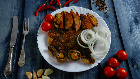 Steak with Idaho potato on a white plate. Blue background. Food on a wooden countertop. Steak with Idaho potatoes on a white plate. Blue background. Eating on a wooden countertop. Фото со стока