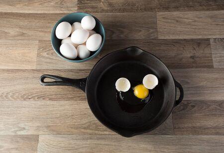 yoke: Raw eggs in frying pan with yoke showing.