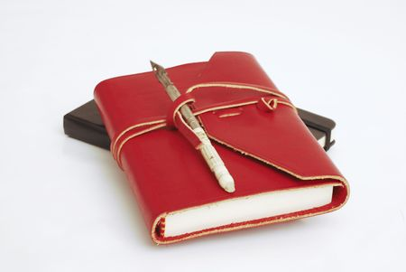 An old red diary with a calligraphy pen on top -  white background