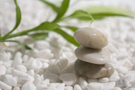 zen stones and bamboo on white pebbles background - meditation concept photo