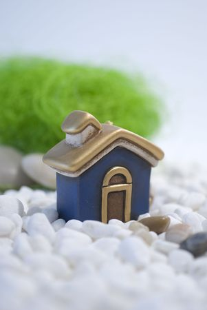 House miniature standing  on white pebbles Home concept photo