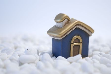 House miniature standing  on white pebbles Home concept