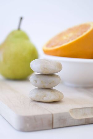 zen stones, orange, and pear on background Stock Photo