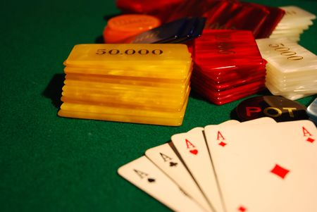 Cards and poker chips arranged on green felt photo