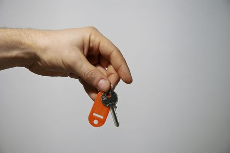 Hand holding keys, blue, grey in the background