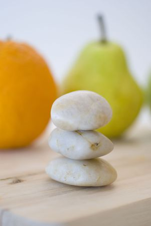 zen stones and orange, apple, pear fruits on background photo