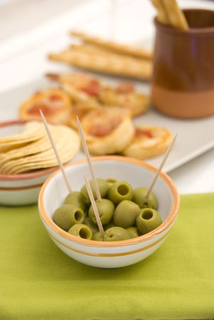 White wine in fine glass with mini pizzas and green olives photo
