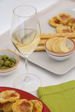 mini pizza: White wine in fine glass with mini pizzas and green olives Stock Photo