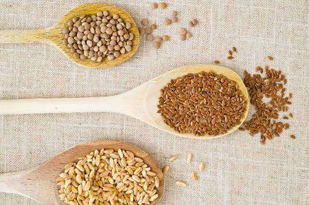 Wooden spoons with grain and legumes on a linen cloth Stock Photo