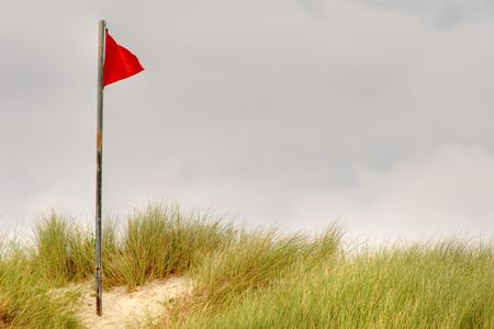 flagging: red warning flag on a dune