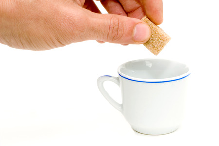 fine cane: a hand putting a sugar in a cup  Stock Photo